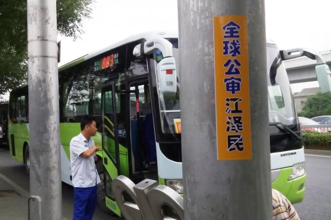 Плакат с надписью «Мир привлекает Цзяна к суду» на столбе в Пекине. Фото: Minghui.org