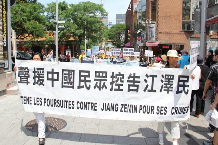 Надпись на плакате: «Поддерживаем жителей китайских граждан, подавших иски на Цзян Цзэминя». Город Монреаль, Канада. Июль 2015 года. Фото: The Epoch Times