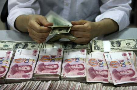 TO GO WITH STORY BY JULIEN GIRAULT This picture taken on September 24, 2013 shows US dollar notes being counted next to stacks of Chinese 100 yuan (RMB) bank notes at a bank in Huaibei, in eastern China's Anhui province. With deals from London to Singapore, China is seeking to have its yuan currency used more widely around the world and challenge the hegemony of the almighty dollar.    CHINA OUT     AFP PHOTO        (Photo credit should read STR/AFP/Getty Images)