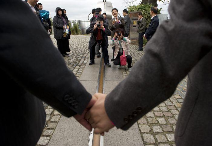 Туристы фотографируют друзей, держащихся за руки через меридиан, Королевская обсерватория, Гринвич, Лондон. Фото: ADRIAN DENNIS/AFP/Getty Images