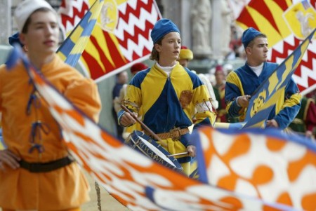 "SIENA, ITALY - AUGUST 15:   Standard bearers of the 'Contrade' (districts) of Palio Siena, dressed in traditional medieval costume during the ""Palio di Siena""  August 15  2002 in Siena, Italy. The medieval horse race and pageant pays homage to the Madonna and pits the ancient districts of Siena, located about 180 kilometers (112 miles) northwest of Rome, against each other for the victory banner.  (Photo by Franco Origlia/Getty Images)"