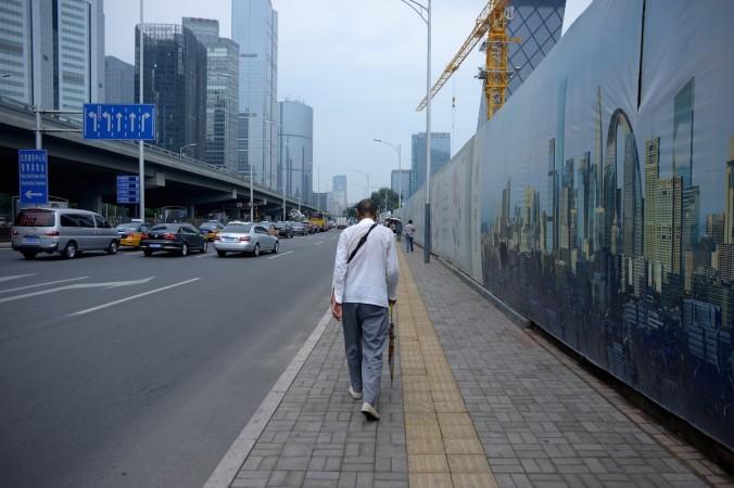 Человек проходит мимо строительной площадки в Пекине 28 июля 2015 года. В последние годы Китай использует грандиозные, но бесполезные проекты для стимуляции роста ВВП. Фото: WANG ZHAO/AFP/Getty Images