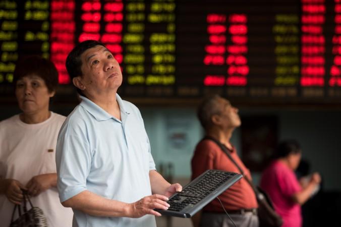 Инвесторы в брокерской фирме в Шанхае смотрят на экраны, показывающие изменения на фондовом рынке, 13 августа 2015 года. Фото: Johannes Eisele/AFP/Getty Image