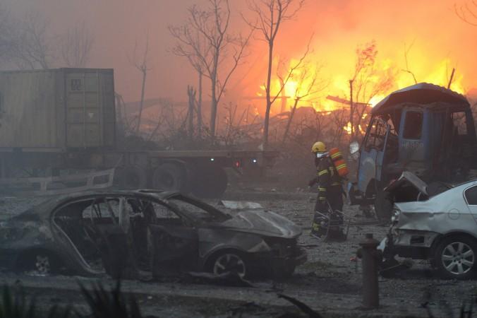 Пожарный проходит мимо искорёженных автомобилей после серии взрывов в городе Тяньцзинь, 13 августа 2015 года. Фото: STR/AFP/Getty Images
