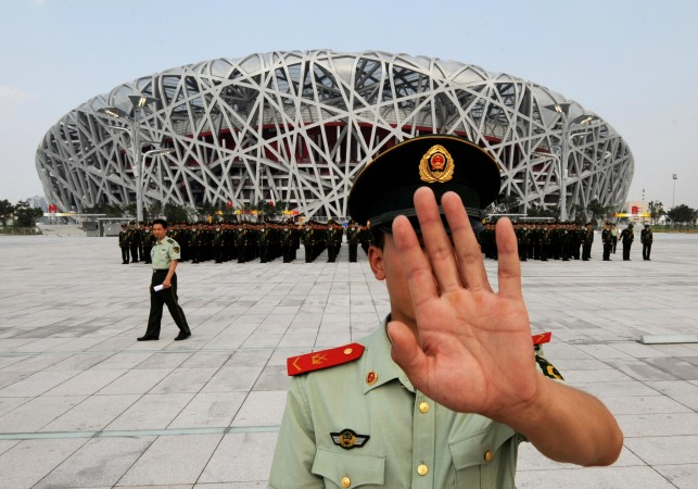 Китайский полицейский не даёт фотографировать репетицию военного парада у олимпийского стадиона в Пекине 21 июля 2008 г. Фото: Mark Ralston/AFP/Getty Images