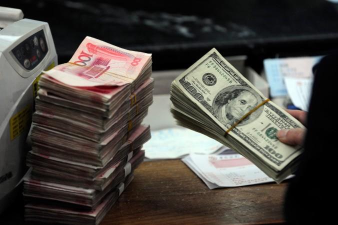 Работник китайского банка готовит пачки долларов и юаней, Хэбэй, провинция Аньхуэй, 9 марта 2010 года. Фото: STR/AFP/Getty Images