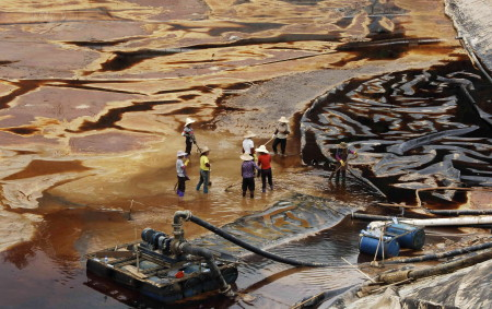Workers drain away polluted water near the Zijin copper mine in Shanghang on July 13, 2010, after pollution from the mine contaminated the Ting river, a major waterway in southeast China's Fujian province. China's top gold producer Zijin Mining defended its handling of a toxic pollution spill that killed off vast numbers of fish, saying heavy rains were to blame, as the company's shares slumped. CHINA OUT AFP PHOTO (Photo credit should read STR/AFP/Getty Images)