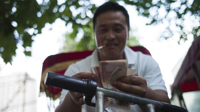 Китаец считает свои деньги, Пекин, 25 августа 2015 года. Фото: Fred Dufour/AFP/Getty Images