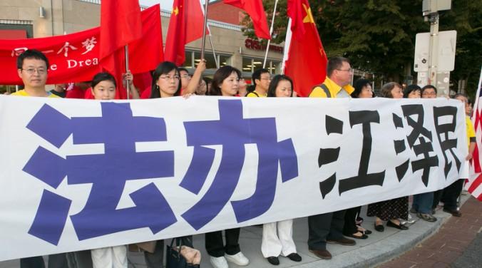 Последователи Фалуньгун держат плакат с надписью «Привлечь к суду Цзян Цзэминя», Вашингтон, 24 сентября. Фото: Lisa Fan/Epoch Times
