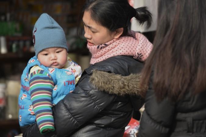 13-месячная девочка гуляет со своей матерью в Пекине, 9 августа 2010 г. Фото: STR/AFP/Getty Images