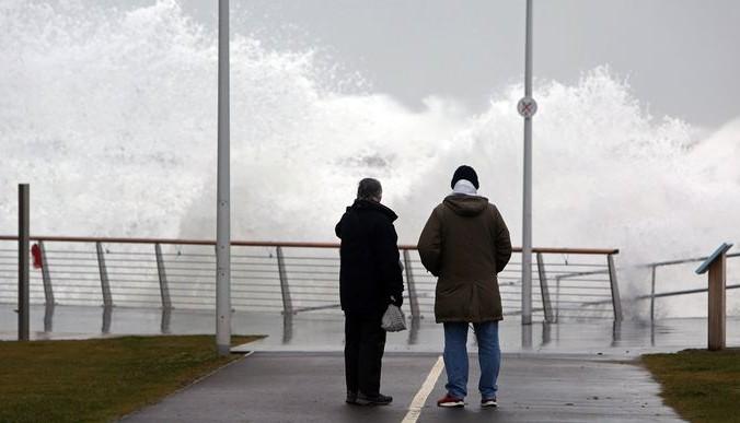 Люди смотрят, как волны обрушиваются на берег моря, в городе Портруш, Северная Ирландия, 9 января 2015 года.  Фото: PAUL FAITH/AFP/Getty Images