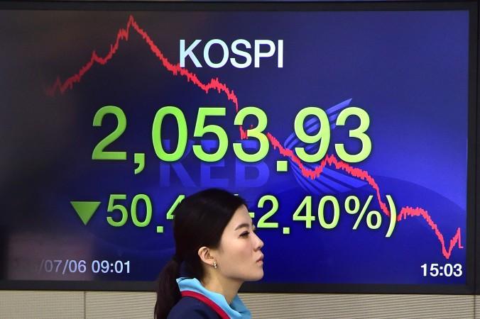 Валютный дилер проходит мимо экрана, на котором показан базовый фондовый индекс Южной Кореи в торговом зале в Exchange Bank Корея в Сеуле на 6 июля 2015 года Фото: Jung Yeon-Je/AFP/Getty Images