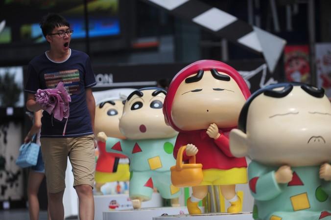 Человек проходит мимо кукол, изображающих героев японской манги Crayon Shin-chan в городе Шэньян, Китай. Фото: STR/AFP/Getty Images