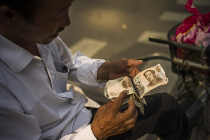 Человек считает китайские юани, Пекин, 28 июля 2015 г.  Фото: Фред Дюфур / AFP / Getty Images