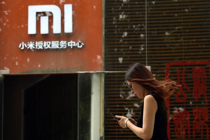 Женщина стоит у сервисного центра Xiaomi в Пекине, 5 августа 2015 года. Фото: Greg Baker/AFP/Getty Images