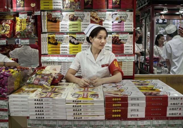 Продавщица в магазине ждёт клиентов 20 января 2015 года, Пекин, Китай. Фото: Kevin Frayer/Getty Images