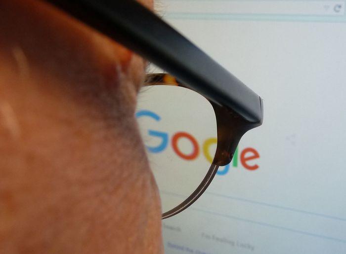 Журналист смотрит на обновлённый логотип компании Google. 1 сентября 2015 года. Фото: EVA HAMBACH/AFP/Getty Images