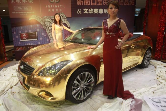 Модель позирует на фоне золотого спортивного автомобиля Infiniti, Нанкин, провинция Цзянсу, 31 марта 2011 года. Фото: STR/AFP/Getty Images