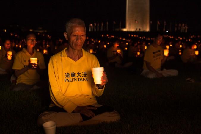Последователи Фалунь Дафа (также Фалуньгун) проводят акцию с горящими свечами в память 16-й годовщины преследования в Китае, Вашингтон, 16 июля 2015 года. Фото: Petr Svab/Epoch Times