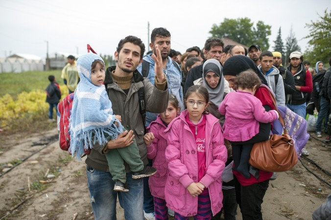 Мигранты и беженцы стоят в очереди, чтобы войти после пересечения границы с Грецией в лагерь в Македонии, около Гевгелии, 8 октября 2015 года. Фото: Robert Atanasovski/AFP/Getty Images