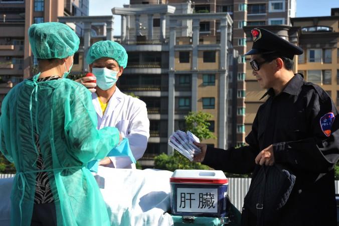 Последователи Фалуньгун проводят инсценировку извлечения органов во время информационной акции в Тайбэе 20 июля 2014 год. Фото: Mandy Cheng/AFP/Getty Images