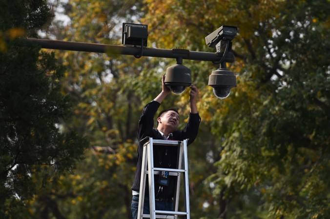 Работник поправляет камеру видеонаблюдения на площади Тяньаньмэнь в Пекине 30 сентября 2014 года. Фото: Greg Baker/AFP/Getty Images