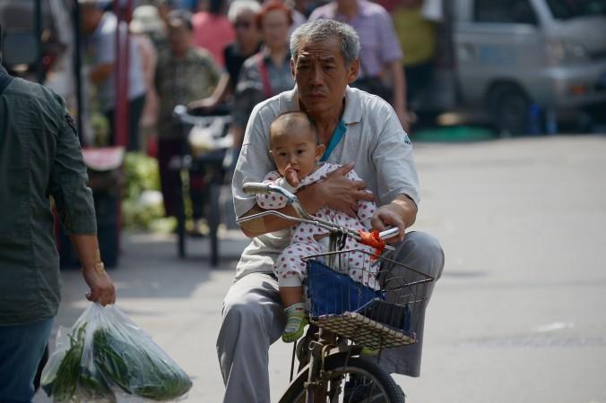 Пожилой человек едет с младенцем на велосипеде по Пекину, 8 сентября 2015 года. Фото: Wang Zhao/AFP/Getty Images