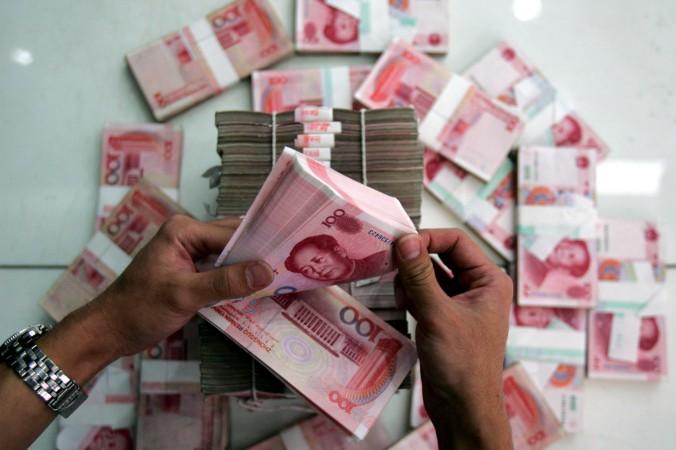 Работник банка пересчитывает юани, Пекин, 22 июля 2005 года. Фото: China Photos/Getty Images