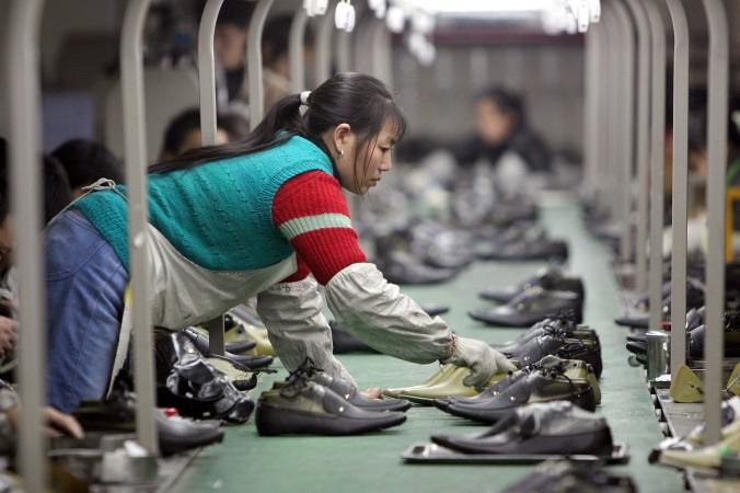 Работница раскладывает обувь по конвейеру на фабрике в городе Чэнду. Фото: China Photos/Getty Images