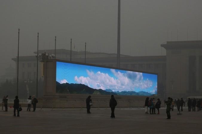 Во время очередной волны смога на большом экране на центральной площади Пекина показывают синее небо. Фото с epochtimes.com