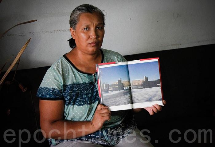 Последовательница Фалуньгун Инь Липин показывает фотографию исправительного лагеря, в котором она подвергалась репрессиям. Фото: The Epoch Times