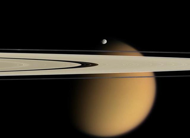 Оранжевый Титан на фоне колец Сатурна. На фото также виден маленький спутник Сатурна - Эпиметей. Фото: NASA