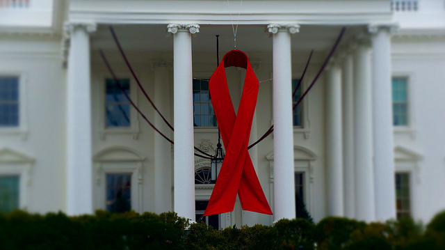 Красная ленточка висит на белом доме в День борьбы со СПИДом 1 декабря. Ленточка является символом солидарности с ВИЧ-положительными людьми и живущими со СПИДом. Фото: Фото: Ted Eytan/flickr.com/CC BY-SA 2.0