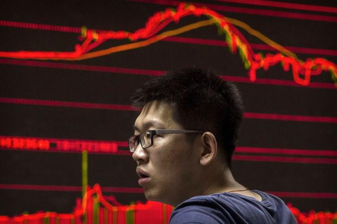 Китайский трейдер смотрит на котировку акций 27 августа 2015 г., Пекин, Китай. Фото: Kevin Frayer/Getty Images