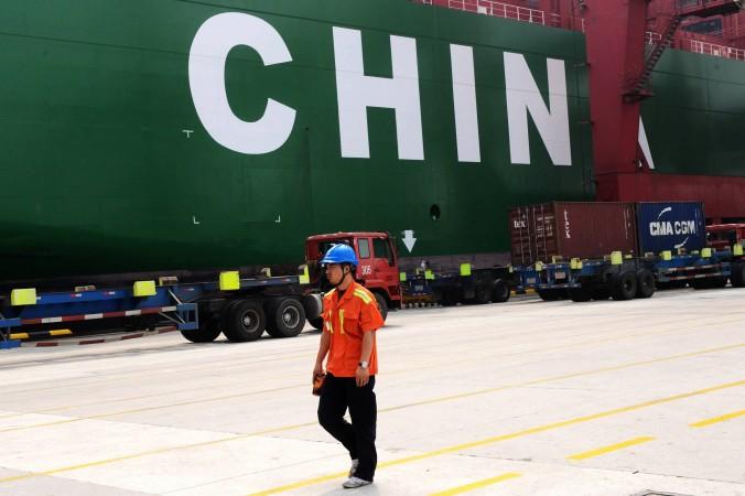 Рабочий проходит мимо грузового корабля в порту Циндао, Китай, 13 октября. Фото: STR/AFP/Getty Images
