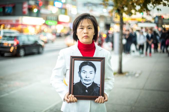 Цзян Ли с фотографией своего покойного отца Цзян Сицина во Флашинге 1 ноября 2015 года. Фото: Бенджамин Chasteen /Великая Эпоха