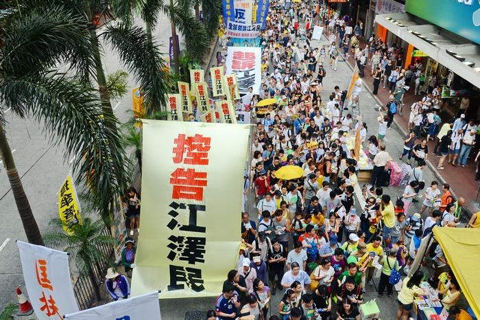 Надпись на транспаранте: «Предъявим иск Цзян Цзэминю». Гонконг. Июль 2015 года. Фото: minghui.org