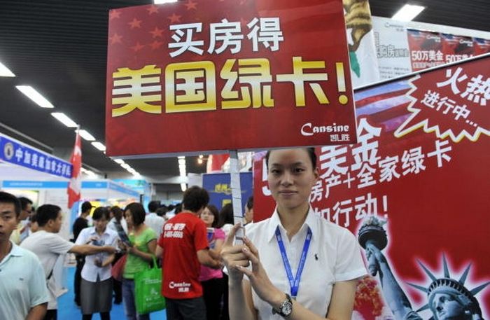Надпись на плакате у девушки: Купи квартиру и получи американскую «грин карту». Фото: AFP/Getty Images