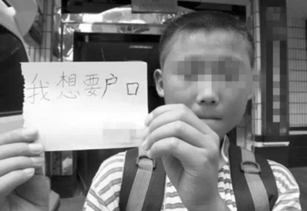 Китайский мальчик держит листок с надписью: «Мне нужна прописка». Фото с epochtimes.com