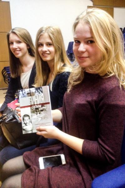 Девушка держит в руке сборник воспоминаний под названием «Линия судьбы». Фото: Юлия Карпова