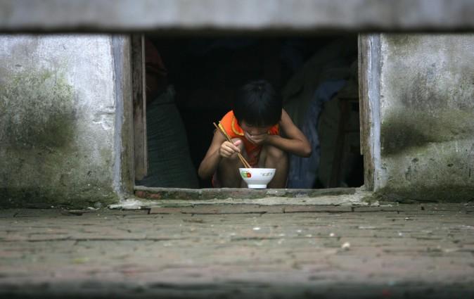 9-летний Дин Шаонань обедает в приюте деревни Саншилипу, провинция Аньхуэй. Дети рабочих-мигрантов, уехавших из деревень в города, часто остаются без присмотра. Фото: China Photos/Getty Images