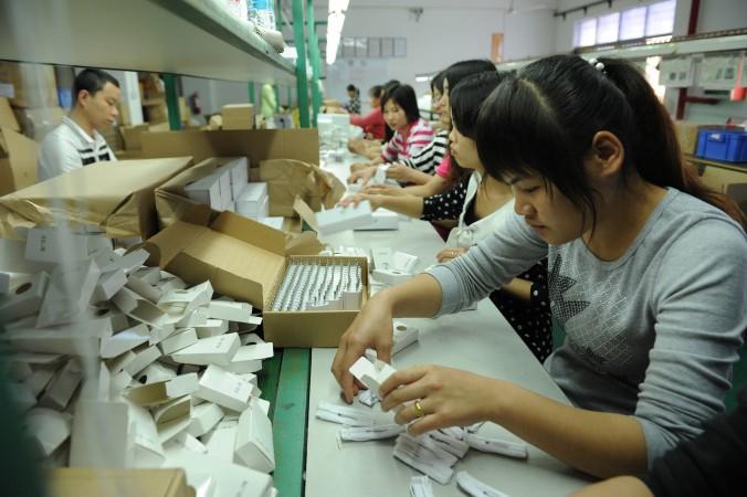 Китайские рабочие упаковывают электронные сигареты на фабрике в Щэньчжэне, провинция Гуандун. Фото: STR/AFP/Getty Images