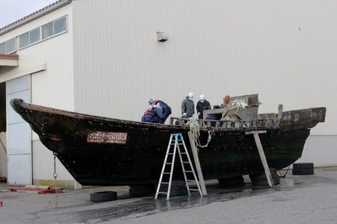 На этом фото, снятом 24 ноября 2015 г. японская береговая охрана изучает деревянную лодку в порту Фукуи в городе Сакаи, западная Япония. За последние два месяца к побережью Японии прибило дюжину странных судов с разложившимися телами моряков. Некоторые СМИ сообщили о северокорейском происхождении лодок. Фото: JIJI PRESS/AFP/Getty Images