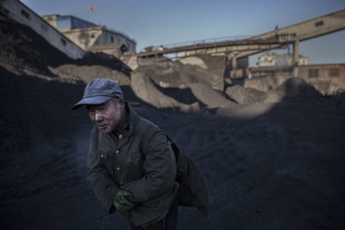 Китайский рабочий несёт уголь с шахты в Шаньси, 25 ноября 2015 г. Фото: Kevin Frayer/Getty Images