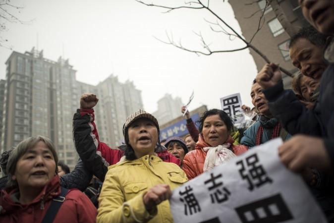 Сторонники правозащитника Пу Чжицяна держат плакат с надписью «Пу Чжицян ― невиновен», Пекин, 14 декабря 2015 г. Фото: Fred Dufour/AFP/Getty Images