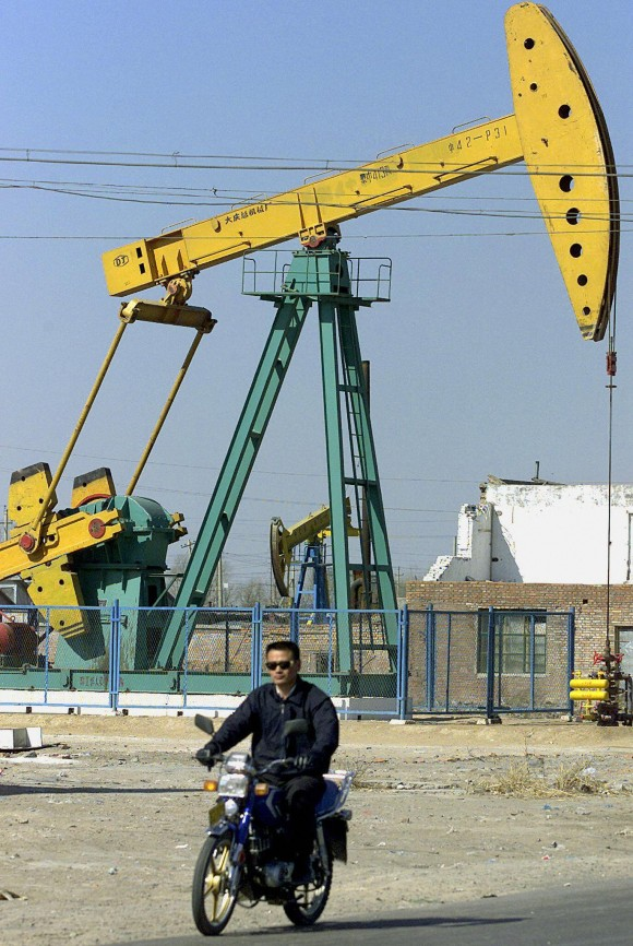 Местный житель едет мимо нефтяного месторождения в Дацине, март 2002 г. Фото: LIU JIN/AFP/Getty Images