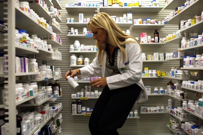 Фармацевт в Майами берёт бутылку антибиотиков с аптечной полки. Фото: file photo, Joe Raedle/Getty Images