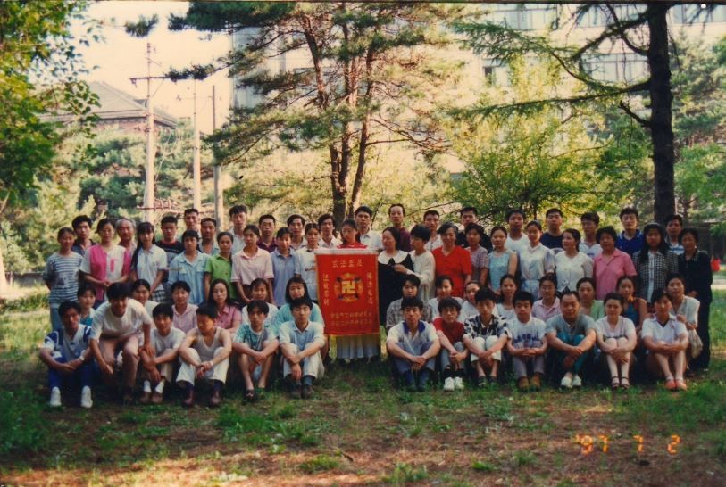 Чэ Пинпин (6-я слева, 2-й ряд) и Ван Хойлянь (2-я слева, 3-й ряд) на пункте выполнения упражнений Фалуньгун у Северо-восточного педагогического университета, 2 июля 1997 года. Фото предоставлено Ван Хойлянь