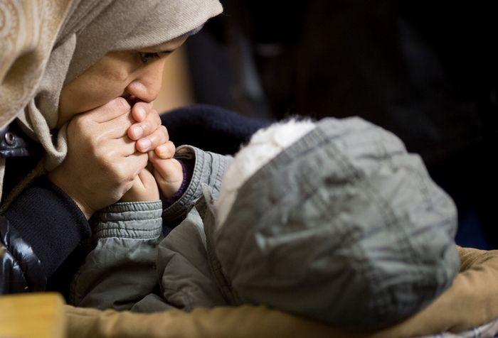 Мать пытается отогреть руки ребёнку в ожидании очереди в Регистрационный центр, температура воздуха минус 11 градусов, Берлин, январь, 2015. Фото: KAY NIETFELD / AFP / Getty Images