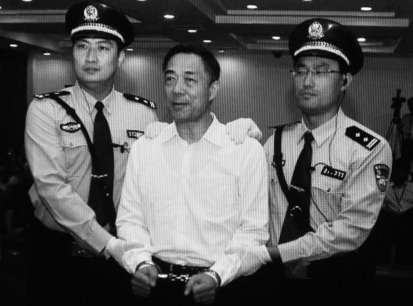 Бывший член политбюро Бо Силай (в центре) в наручниках